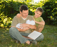 Mature father with a newborn baby in his hands reading book with. His elder son on the lawn in the garden. Family reading together. Summer holiday. Happy family stock photos