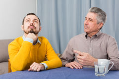Mature father and son serious talk Royalty Free Stock Image