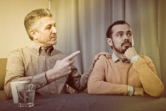 Mature father and son serious talk Royalty Free Stock Images