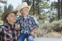 Mature father and son wearing cowboy hats looking away in park Stock Images