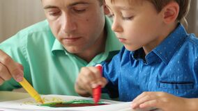 A mature father spends time with his young son, drawing with colored pencils.Close up. The concept of a happy family