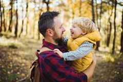 A mature father holding a toddler son in an autumn forest, talking. royalty free stock image