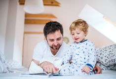 Father with toddler boy reading a book on bed at home at bedtime. Mature father with toddler boy in bedroom at home, reading stories at bedtime. Paternity leave Royalty Free Stock Photo