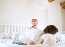 Father with a toddler boy having fun in bedroom at home at bedtime. Mature father with a toddler boy having fun in bedroom at home at bedtime. Paternity leave Royalty Free Stock Images