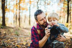 A mature father and a toddler son in an autumn forest, taking pictures with a camera. stock image