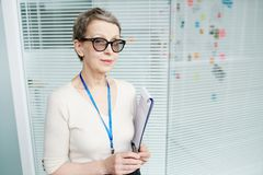 Mature FBI Agent at Work. Waist-up portrait of beautiful mature FBI agent in eyeglasses looking at camera while wrapped up in criminal investigation, she holding Stock Photo