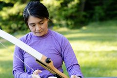 Mature Female Archer Holding Bow In Forest. During training Royalty Free Stock Image