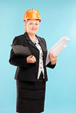 Mature female architect holding plans Stock Images