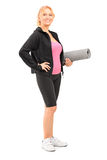 Mature female athlete holding a mat Royalty Free Stock Photo