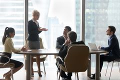 Mature female manager speaking to executive team at group meeting. Mature female business leader coach board manager speaking to executive team explaining new stock photos