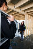 Carpenter Looking At Colleague Carrying Ladder In Incomplete Bui Stock Images