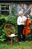 Mature female cellist. Mature female cellist with her instrument outdoors royalty free stock photos