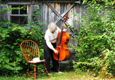 Mature female cellist. Mature female cellist with her instrument outdoors stock photography