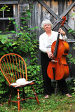 Mature female cellist. Mature female cellist with her instrument outdoors royalty free stock image