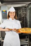Mature Female Chef Presenting Pizza Stock Photos