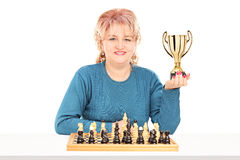 Mature female chess player holding a trophy Royalty Free Stock Photos