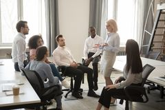 Mature female coach training teaching young employees at team meeting stock photography