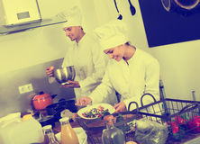 Mature female cook holding plate. Mature female cook wearing uniform holding plate with green salad Stock Image