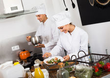 Mature female cook holding plate. Mature female cook wearing uniform holding plate with green salad Stock Photography