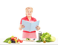 Mature female cooker with apron and book of recipies preparing s Stock Photos