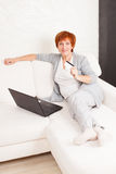 Mature female with credit card and laptop Stock Images