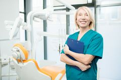 Successful dentist. Mature female dentist or assistant with clipboard inviting you to new dental clinics Royalty Free Stock Photography