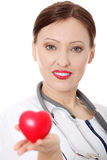 Mature female doctor with heart in her hand. Stock Photography
