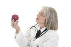 Mature female doctor holding an apple Stock Photos