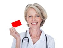 Mature female doctor holding visiting card Royalty Free Stock Photography