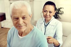Mature female doctor listening to lungs of male patient. Always ready to help. Selective focus on a mature medical specialist looking at a retired gentleman royalty free stock photos