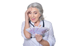 Mature female doctor with money Royalty Free Stock Photos