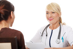 Mature female doctor talking with patient. Royalty Free Stock Photography