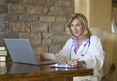 Mature female Doctor writing prescription Royalty Free Stock Photography