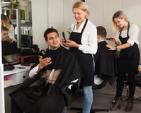 Mature female doing hairstyle for adult man. Mature female doing hairstyle for adult men in hairdressing saloon royalty free stock photo