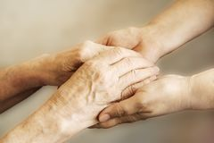 Close up of mature womans & nurse hands. Health care giving, nursing home. Parental love of grandmother. Old age related diseases. Mature female in elderly care royalty free stock photo