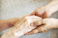 Close up of mature womans & nurse hands. Health care giving, nursing home. Parental love of grandmother. Old age related diseases. Mature female in elderly care royalty free stock photos