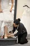 Mature female employee helping bride with footwear in bridal boutique Royalty Free Stock Photo