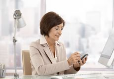 Mature female executive using smartphone in office stock image