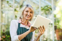 Mature female gardener using tablet computer. Portrait of happy mature female gardener using tablet computer against greenhouse Royalty Free Stock Photos