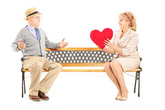 Mature female giving a red heart to a surprised man, seated on a Royalty Free Stock Image