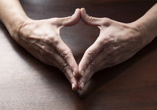 Mature female hands making a heart shape. Talking hands concept - female hands making a heart shape together for love and peace symbol on wooden table,studio royalty free stock images