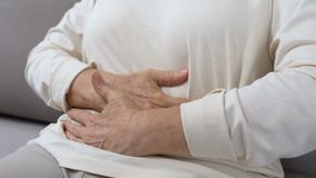 Mature female holding hands on tummy, abdominal pain, gastritis health problem