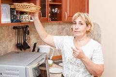 Mature female in kitchen. Mature woman standing in kitchen with breadbasket stock image