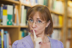 Mature female librarian giving a sign to be quiet standing in library royalty free stock image
