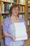 Mature female librarian posing holding a pile of books Royalty Free Stock Photos