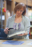 Mature female librarian scanning book Royalty Free Stock Photos
