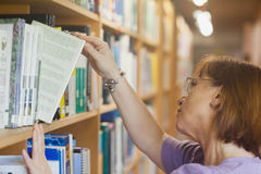 Mature female librarian searching a book Stock Photography
