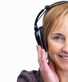 Mature female listening to music on headphones Stock Photography