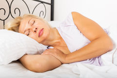 Mature female in pajamas sleeping Stock Image