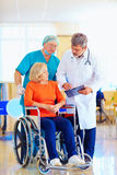 Mature female patient on wheelchair listens to doctor prescription medication stock image